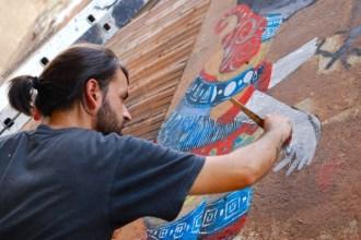 Skount trabajando en el mural con pincel