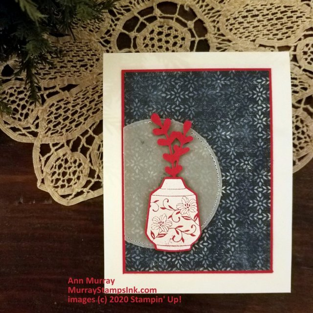 White embossed red vase with red sprig on blue patterned background