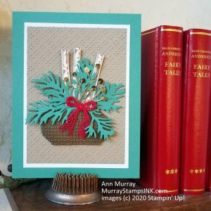 Holiday arrangement with birch logs and gold berries on embossed background
