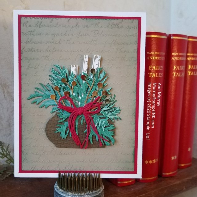 holiday green arrangement with birch logs on script background