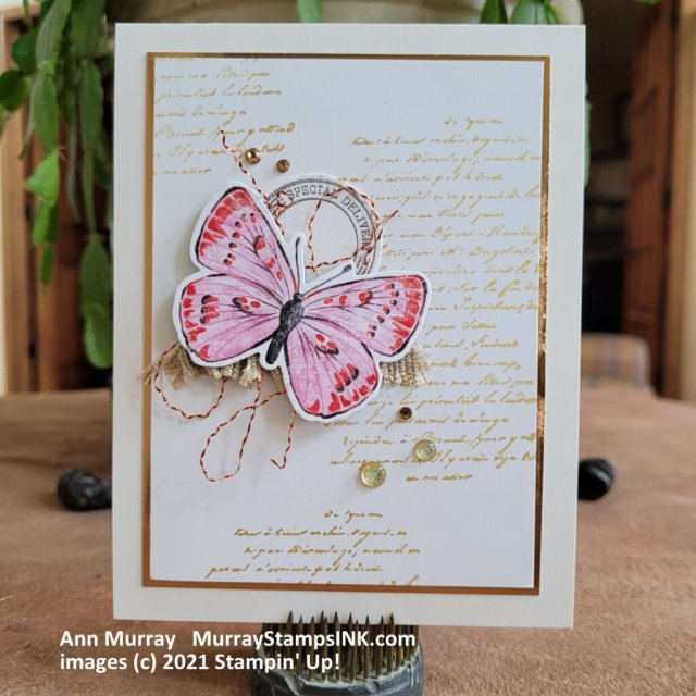 butterfly layered with copper thread on a background stamped with gold script