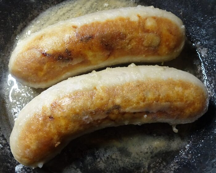 小麦粉をまぶせたシレジア風ソーセージを最弱火でじっくりと炒める