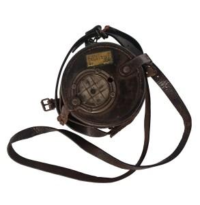 Photographie de l'appareil contrôleur de rondes du théâtre des célestins : un boitier de cuir contenant un mécanisme d'horloge en métal.