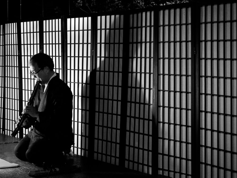 Japanese shakuhachi performer in front of a screen in black and white