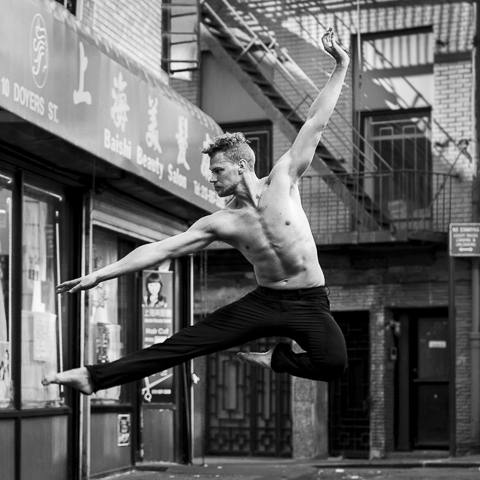 male ballet dancer jumping in the street