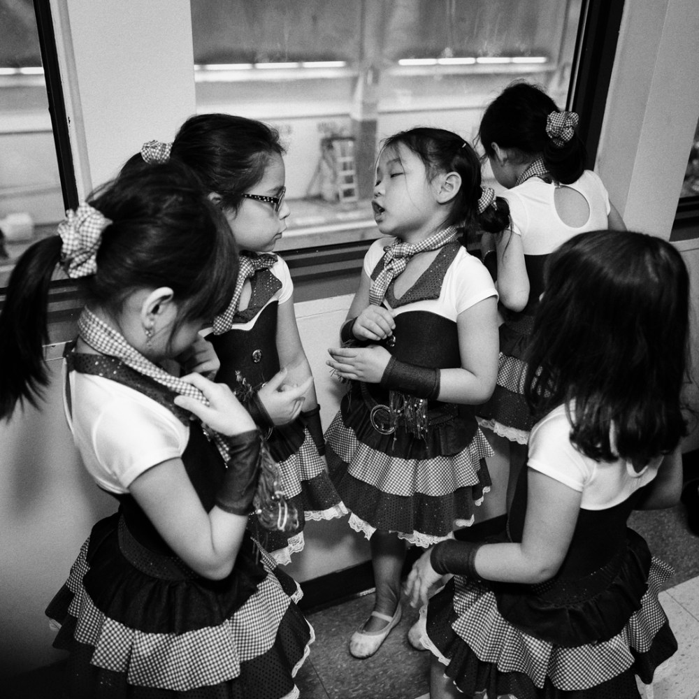 black and white candid shot of young girl dancers talking