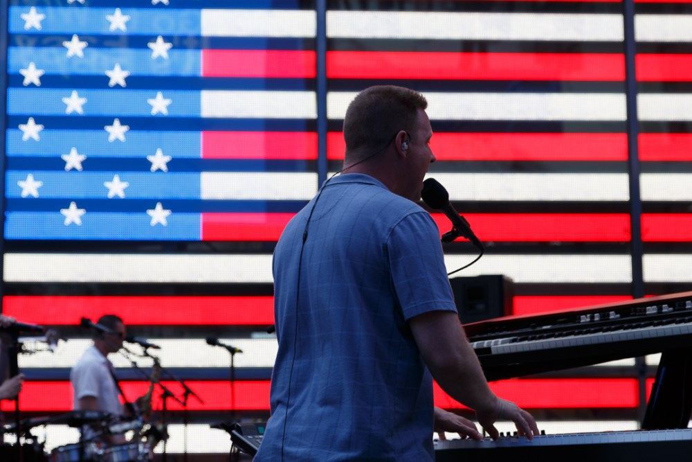 US Navy band keyboard player in front of Times Square American flag