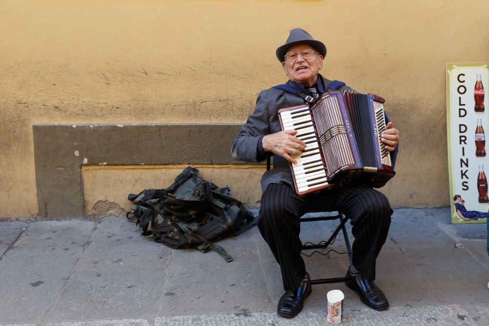 old man playing accordion in front of yellow wall
