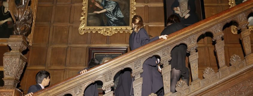 Children in school uniform are climbing the staircase at temple newsam.