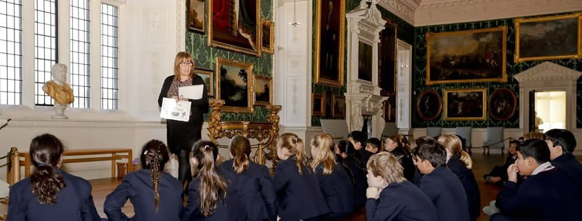 School children are sat on the floor in the picture gallery at temple newsam, listening to a learning officer.