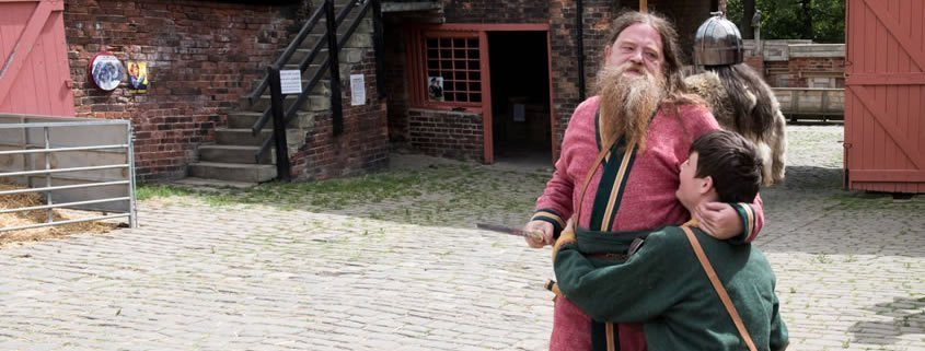 A man dressed as a viking is play fighting with another man dressed as a viking.