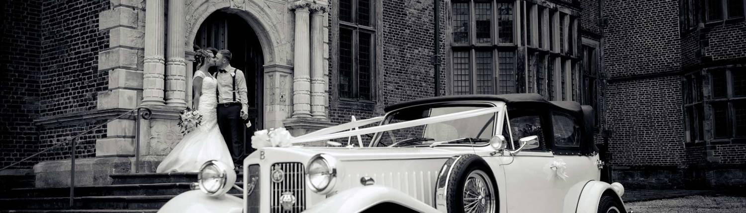 A black and white photograph of a bride and groom kissing on the steps of temple newsam next to a wedding car.