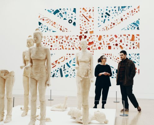 Two people are chatting in a white gallery. There is a union jack artwork on the wall, and sculptures of a young girl figure in front of them.