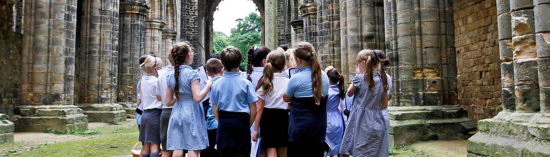Group of school children inside Kirkstall Abbey