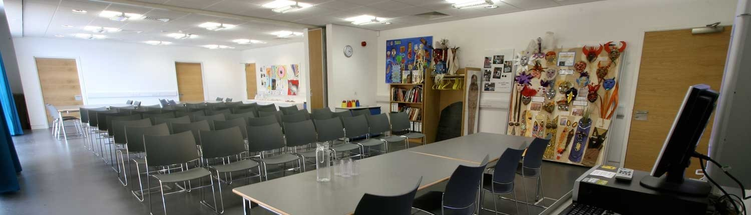 Classroom with several rows of chairs, masks on the wall and a table with a computer on