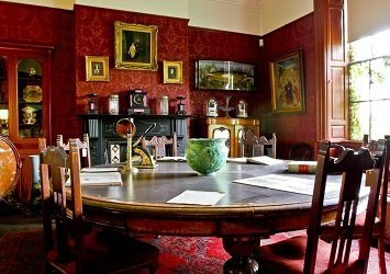 Round table surrounded by six chairs in a room with rich red wallpaper, carpet and paintings hanging on the wall