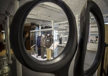 Outfits in display cases, pictured through the handle of a pair of scissors