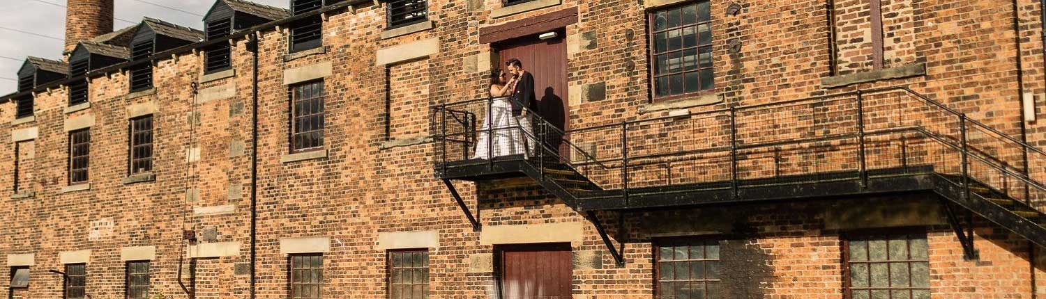 Couple in wedding attire standing on a stairwell outside Thwaite Watermill