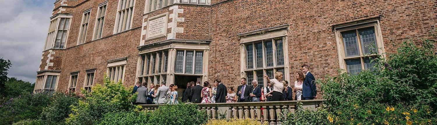 Wedding guests standing on a balcony at Temple Newsam