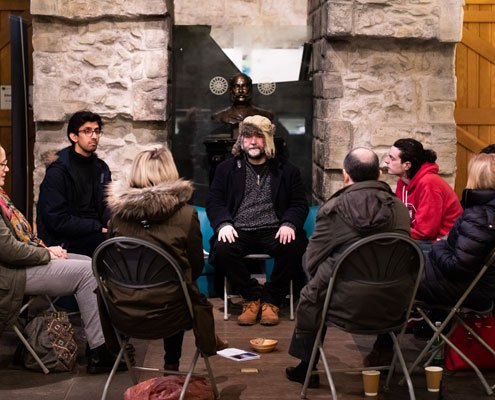 A group of adults sat in the Colonel North room at Kirkstall Abbey as part of a mindfulness session