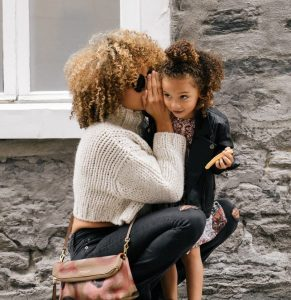 mom whispering to child things to say to your child every day
