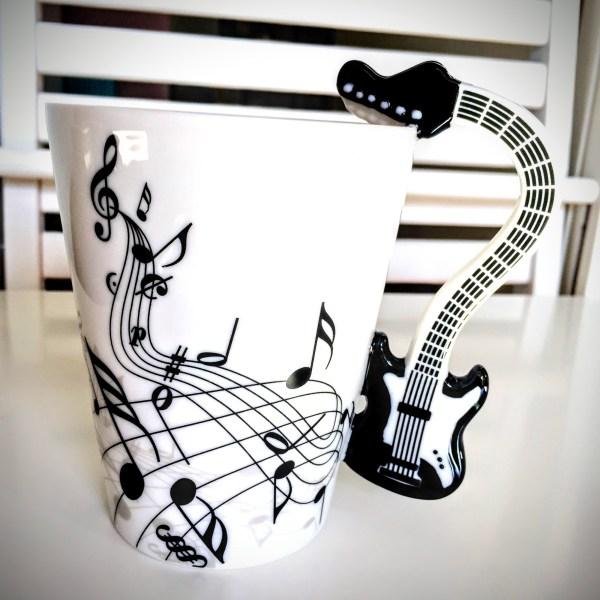 Голяма чаша с дръжка на черна електрическа китара или шестструнна бас китара