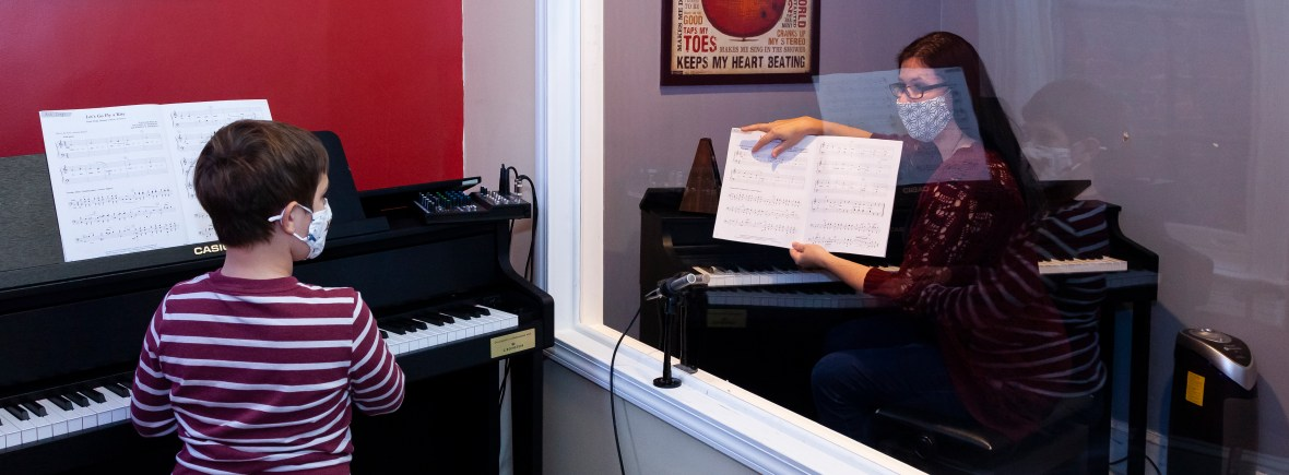 Piano lesson with full wall barrier with clear window