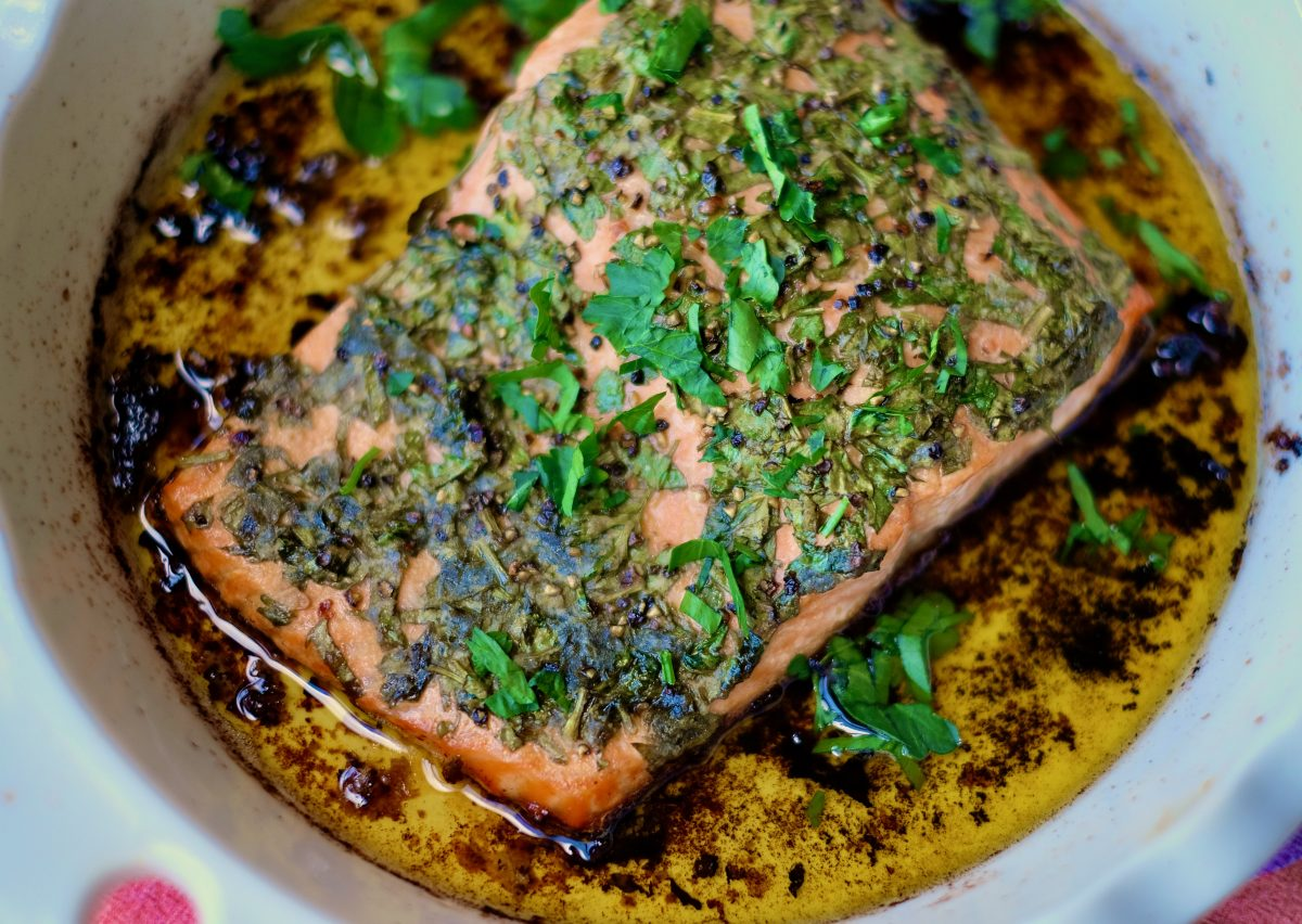 One piece of baked trout in a white baking dish
