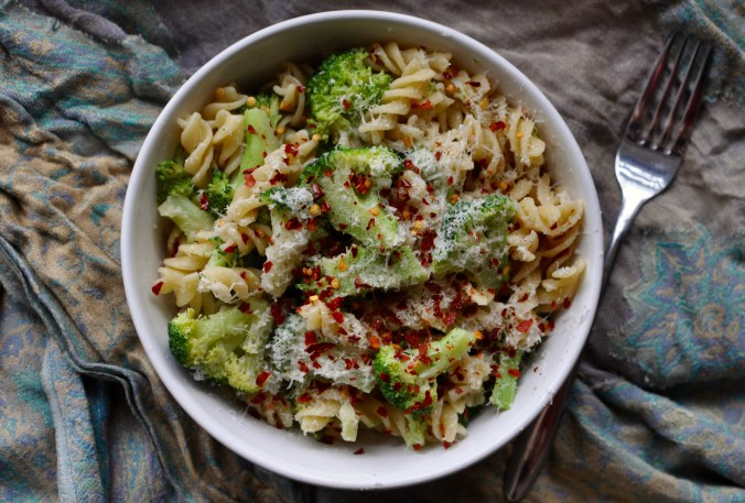Bowl of rotini pasta with broccoli, chillies, and parmesan.