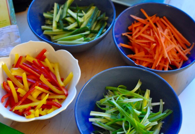 Cut up vegetables for salad rolls on bowls