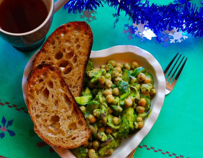 Heart-shaped plate full chickpea and cucumber salad and 2 pieces of sour dough toast.