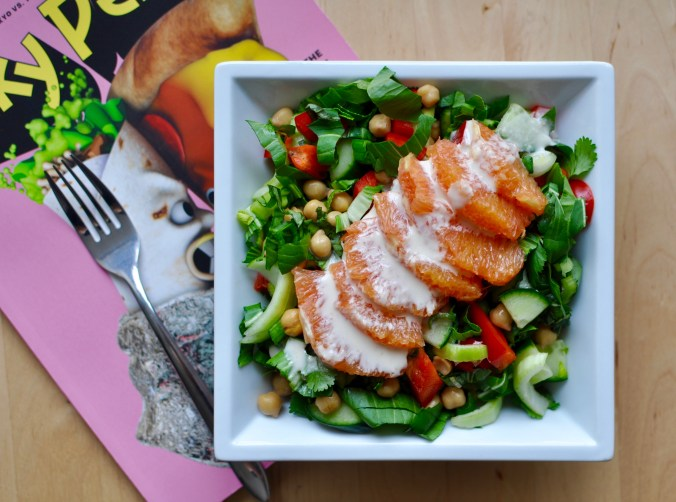 A white square plate full of salad containing chickpeas, bok choy, red peppers, and orange slices covered with a tahini orange dressing. A copy of Lucky Peach is in the background.