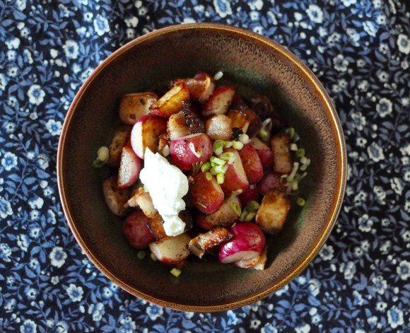 A brown shallow bowl full of roasted radishes, bacon, scallions and a small tablespoon of skyr on top.