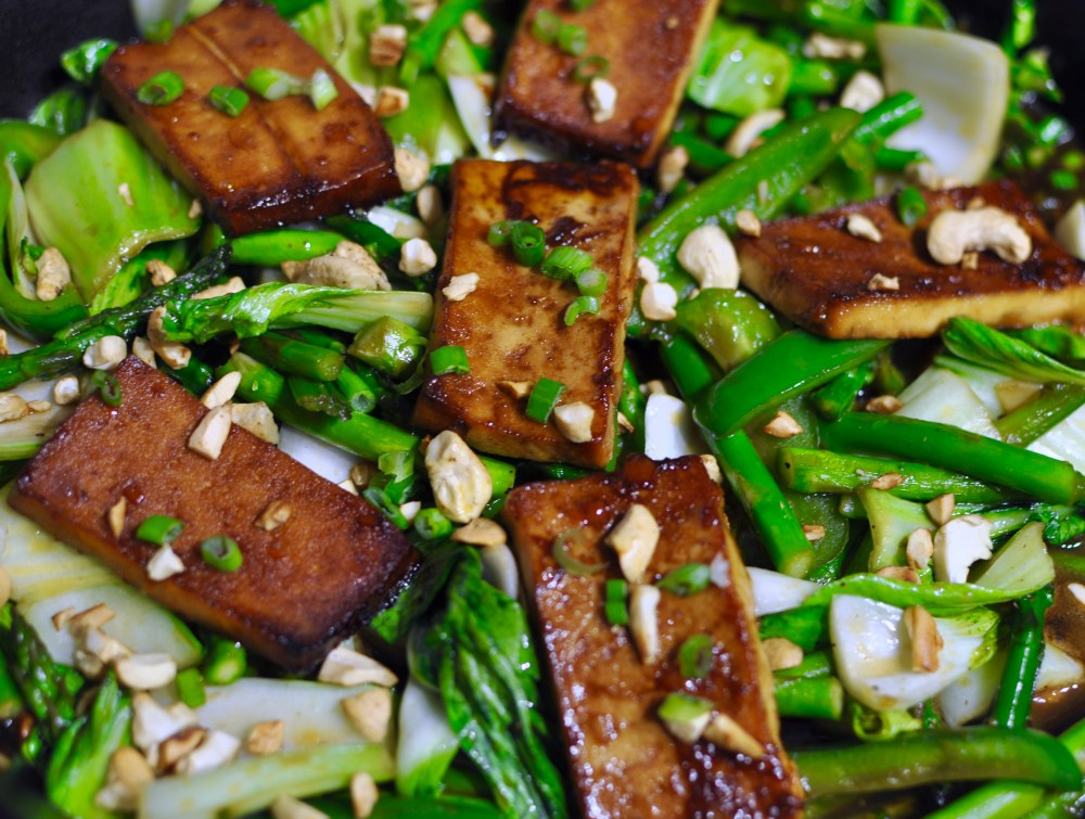 Big skillet full of stir fried bok choy, asparagus, scallions, and baked hoisin tofu. Topped with toasted cashews.