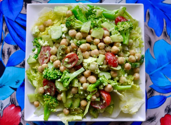 Broccoli, chickpeas, grape tomatoes, pickled peppers, cucumbers and a creamy feta and avocado dressing on a bed of lettuce.