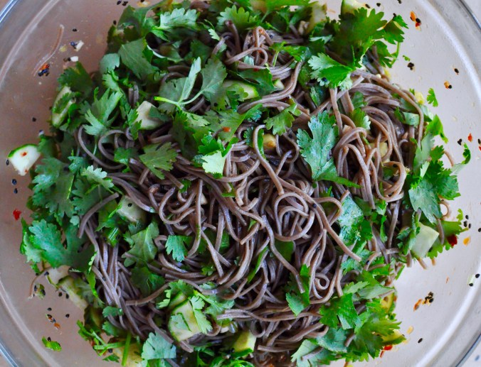 Salad bowl full of simple cold soba noodle salad with cilantro, cucumber, and chilies.