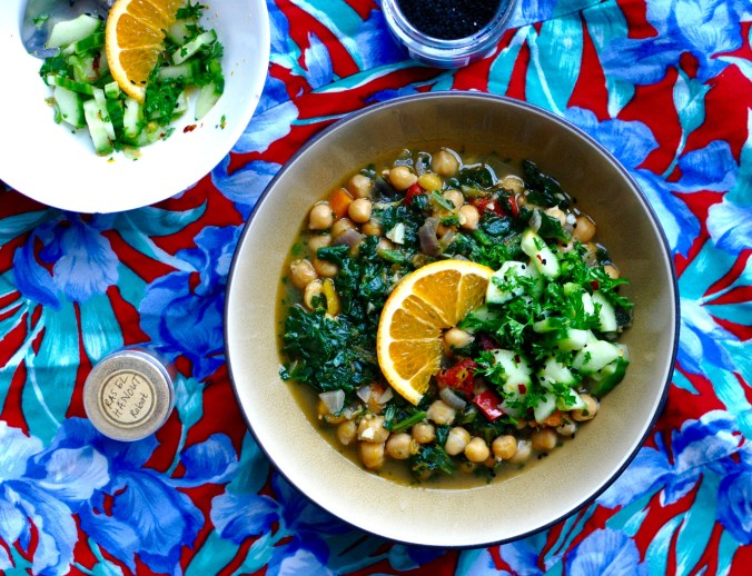 spiced chickpea stew with butternut squash and spinach in a shallow brown bowl, a small white bowl to the side holds a cucumber slaw to top the stew with. the bowls are arranged on a blue and red tablecloth, with a small pot of ras el hanout and a tub of black nigella seeds.