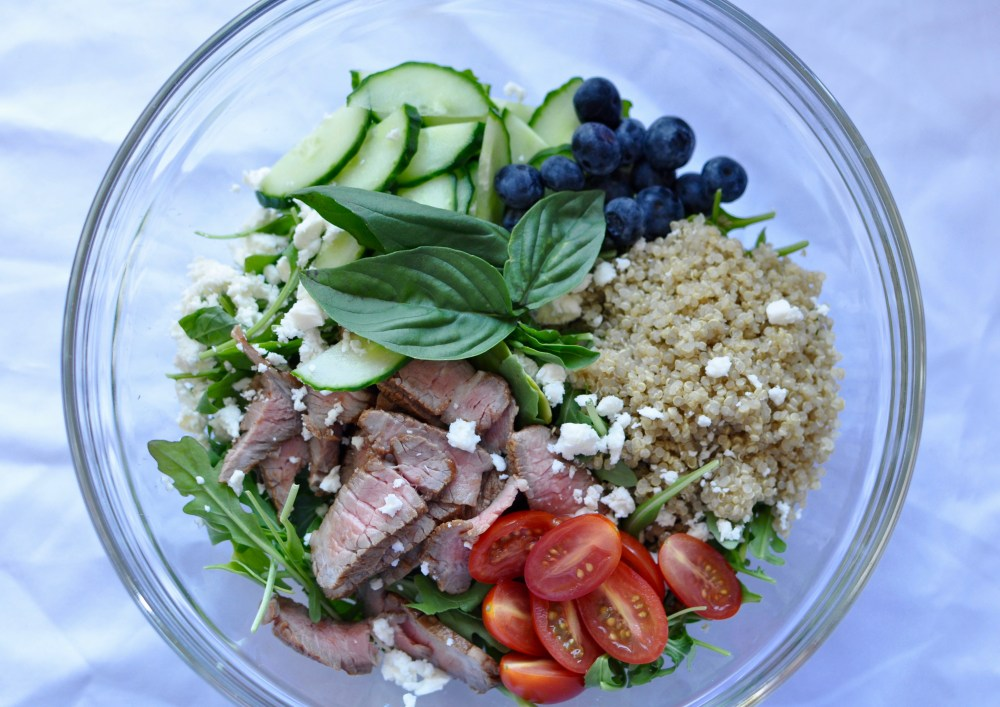 Summer salad of leftover steak, quinoa, blueberries, tomatoes, cucumber, arugula, and feta in a clear glass bowl on a white background.