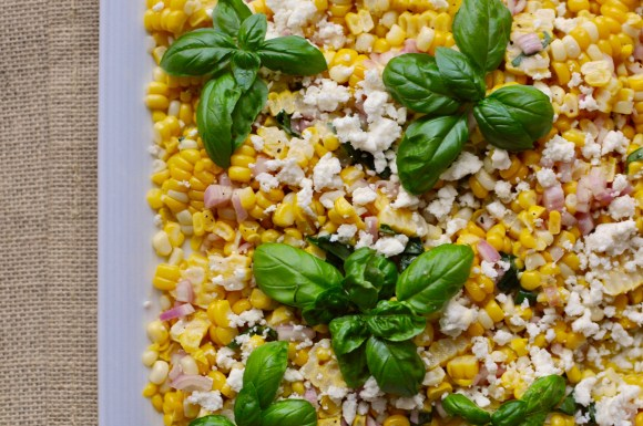 White square plate with sweet corn salad with basil and feta cheese.