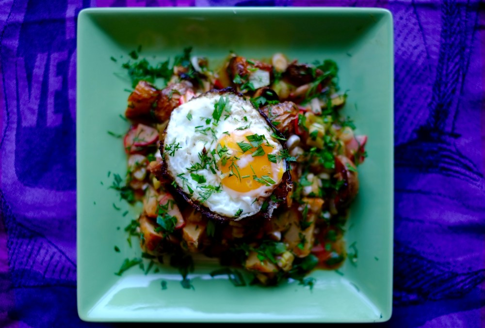 Warm roasted potato salad topped with a crispy egg on a square green plate with a purple background.