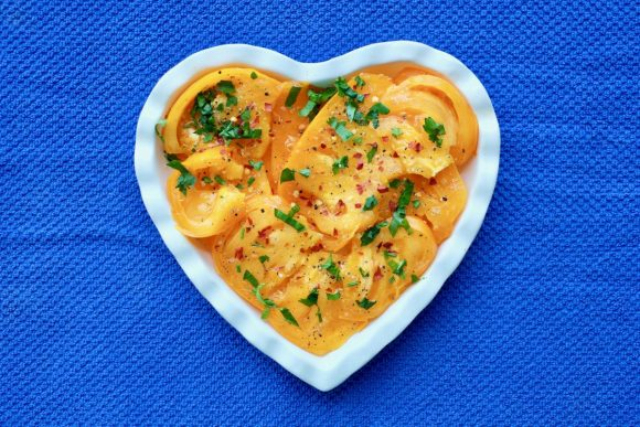 Yellow tomato salad on a white heart-shaped plate on a blue background.