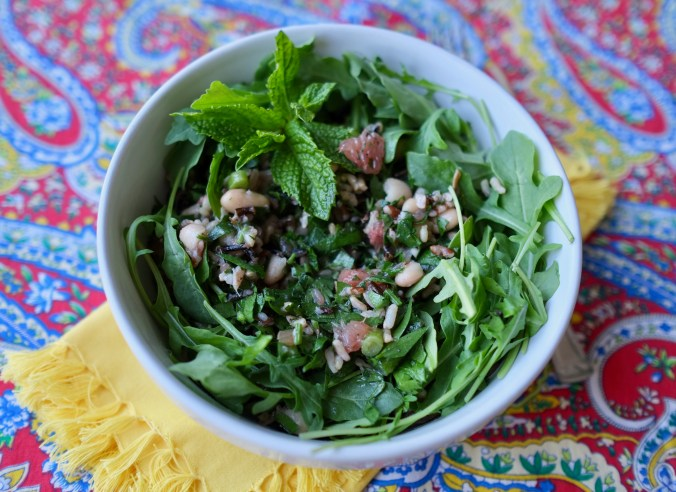 Cannellini bean salad in a round white bowl on a batik-print tablecloth with yellow cloth napkin.