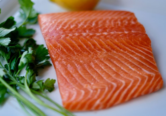 Close-up of a raw trout fillet beside a bunch of fresh parsley on a white background.