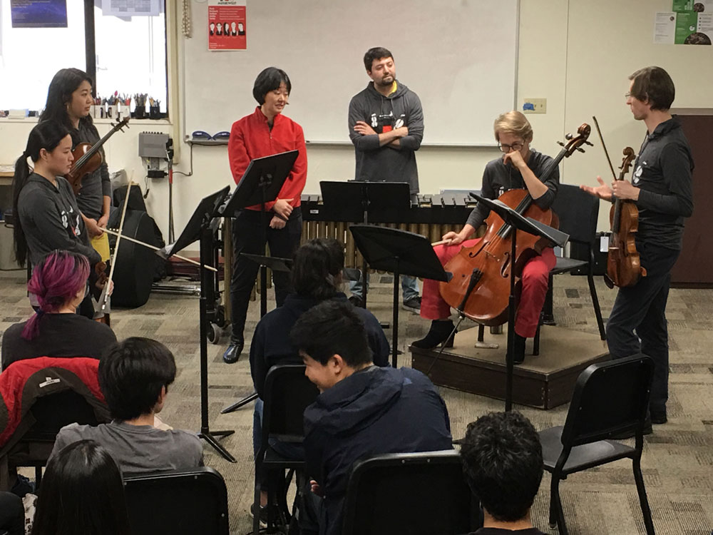"Musikiwest performers working their way through the ""problem"" with Dr. Rona Hu while students look on."