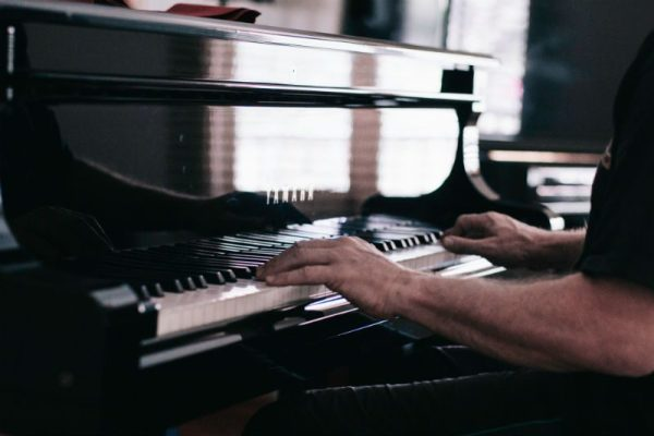Man learning to play the piano and taking piano lessons Montreal.