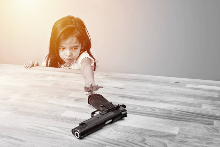 children try to play parent's gun on table
