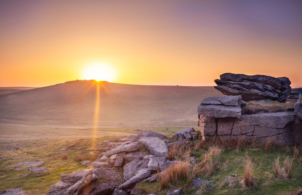 The sun rises behind Great Mis Tor