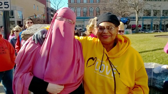 Photo taken by Rev. Charlie Davis and features Gail Schatzie Reynolds Davis and Tuscany Bernier (pink niqab). Photo taken at a local march in Lafayette, Indiana