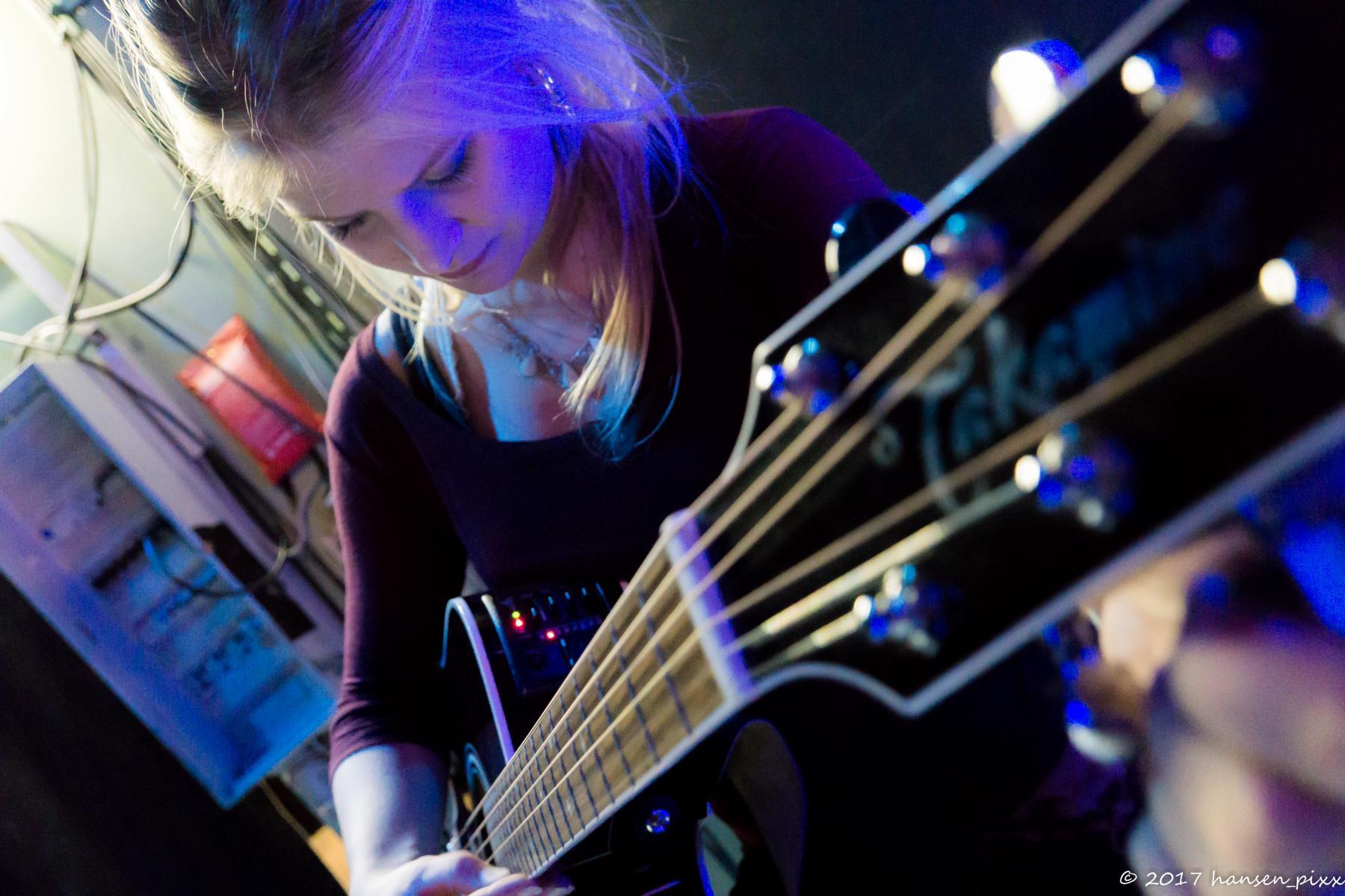 Aynie stimmt ihre Gitarre vor dem Auftritt.