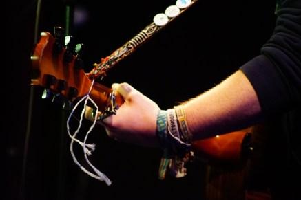 Stilvoll geschmücktes Handgelenk mit stilvoll geschmücktem Gitarrengurt.